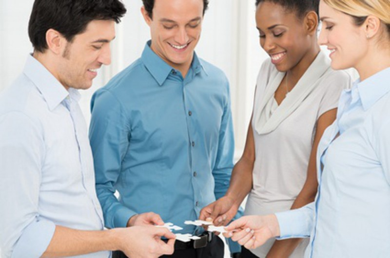 Group Of Happy Businesspeople Holding Jigsaw Puzzle In Hand